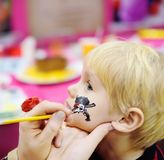 Face painting for cute little boy during kids birthday party. Face painting for cute little boy during kids merriment. Face paint for `Pirates` theme on birthday Stock Photo