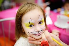 Face painting for cute little girl during kids birthday party. Face painting for cute little gorl during kids merriment. Face paint for `Animals` theme on stock photos