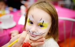 Face painting for cute little girl during kids birthday party royalty free stock photo