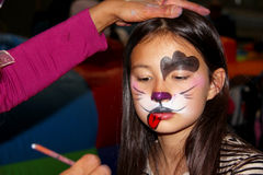 Face painting dog. A pretty little girl having face painting done to turn her into a little dog stock images