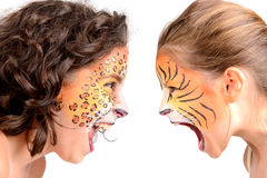 Face painting, felines. Beautiful young girls with feline painted faces, tiger and leopard royalty free stock photos