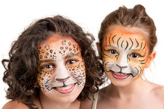 Face painting, felines. Beautiful young girls with feline painted faces, tiger and leopard stock photos