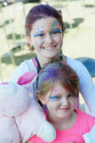 Face Painting. Girls with beautiful face painting and hair coloured blue and purple with fun hairspray royalty free stock photos