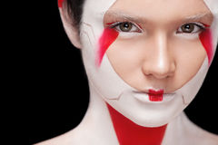 Face Painting in Japan style. Body art colorful make-up. Geisha isolated on black background. Stock Image