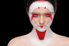 Face Painting in Japan style. Body art colorful make-up. Geisha isolated on black background. Portrait of the bright beautiful emotional woman with art make-up royalty free stock photography