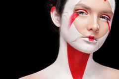 Face Painting in Japan style. Body art colorful make-up. Geisha isolated on black background. Portrait of the bright beautiful emotional woman with art make-up royalty free stock photos