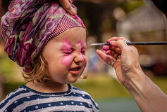 Face painting. Little girl having her face painted during local fair royalty free stock photography