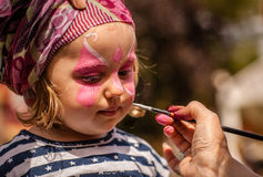 Face painting. Little girl having her face painted during local fair royalty free stock image