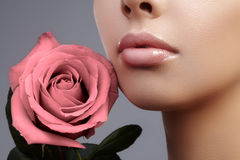 Face part. Beautiful female lips with natural makeup, clean skin. Macro shot of female lip, clean skin. Fresh kiss. Royalty Free Stock Photo