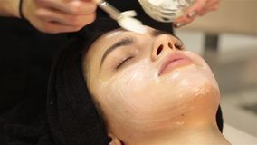 Face peeling mask, spa beauty treatment, skincare. Woman getting facial care by beautician at spa salon. Hd stock video