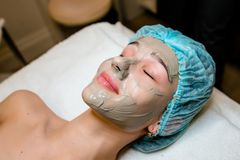 Face peeling mask, spa beauty treatment, skincare. Woman getting facial care by beautician at spa salon.. Face peeling mask, spa beauty treatment, skincare Royalty Free Stock Images