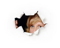 Face peeping out of hole - female curiosity. A woman's face peeping out of hole - the female curiosity stock image