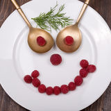 Face on a plate of raspberries Stock Photography