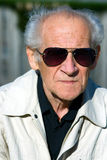 Face Portrait. Of an old serious senior in sunglasses Stock Image