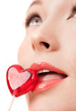 Face portrait of beautiful young woman with heart lollipop Royalty Free Stock Images
