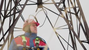 Face portrait of electrician standing on electrical tower background. Face portrait of caucasian adult electrician worker standing on electrical tower background stock video