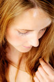 Face portrait of a demure lady. Close up portrait of a shy redhead caucasian woman looking down, with barely any make up - a top down perspective Stock Image