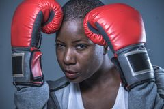 Face portrait of young angry and defiant black afro American sport woman in boxing gloves training and posing as a dangerous figh. Close up face portrait of royalty free stock photography