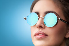 Face portrait of young beautiful woman in round sunglasses. Close-up face portrait of young beautiful woman with perfect skin in round sunglasses looking up on stock image
