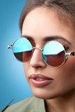 Face portrait of young beautiful woman in round sunglasses smiling. Close-up face portrait of young beautiful woman with perfect skin in round sunglasses smiling stock images