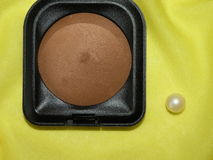 Face powder. On the yellow fabric Stock Photo