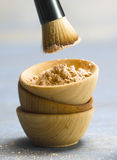 Face Powder. Foundation Powder in a small wooden bowl with a brush over the top on a blue canvas Stock Image