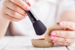 Face powder in female hand Stock Images