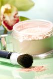 Face powder and orchid flower. Closeup of container of opened face powder, brush and blooming yellow orchid flower on reflected surface stock image