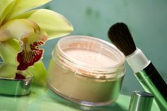 Face powder and orchid flower Royalty Free Stock Photography