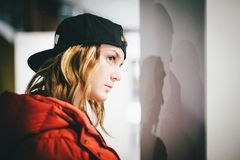 Face profile of trendy girl in red jacket wearing stylish cap royalty free stock photo