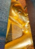 Face of Reclining Buddha gold statue in Bangkok, Thailand Royalty Free Stock Images
