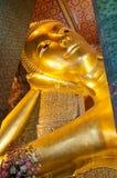 Face of Reclining Buddha gold statue in Bangkok, Thailand Stock Photos