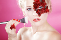 Face with red feathers and a rouge brush Stock Image