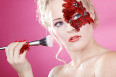 Face with red feathers and a rouge brush Stock Images