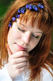 Face of redheaded girl in spring forest. Redheaded girl in the spring forest with flowers in her hair Royalty Free Stock Images