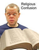 Face of religious confusion. Photo of cross-eyed man with open bible in foreground depicting dumbfounded look of religious confusion! isolated on white ideal for Stock Photography