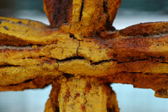 The face of rust. An old window bar, shaped like a cross, covered with rust that looks like a face Stock Photos