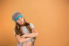 The face of sad teen girl. In hat on brown studio background Stock Photo