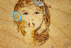 Face in the sand. Face of a little girl in the sand, seaweed for hair. Conceptual photo montage Stock Image