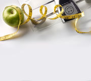 Face scale with apple and tape measure square composition top Stock Images