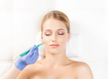 Face with a scalpel. Aging, plastic surgery, and skin rejuvenation concept Stock Photos