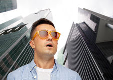 Face of scared man in sunglasses over big city Royalty Free Stock Photo