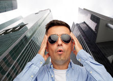 Face of scared man in sunglasses over big city Stock Photography