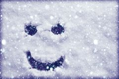 Face scary smiling smiley drawn on white snow, frosty winter day. Close-up. Free space for text stock photo