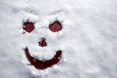 Face scary smiling smiley drawn on white snow, frosty winter day. Close-up. Free space for text stock photos