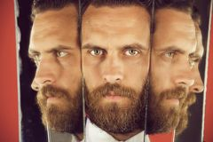 Face of serious bearded hipster man, businessman reflecting in mirror. Face of serious bearded hipster man or businessman reflecting in mirror, multifaceted royalty free stock image