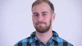 Face of serious bearded hipster man nodding head no. Studio shot of bearded hipster man against white background stock footage