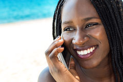 Face shot of african teen girl having conversation on phone. stock photo