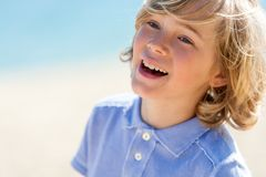 Face shot of laughing boy outdoors. Close up portrait of laughing blond boy outdoors Royalty Free Stock Photography
