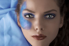 Face shot of a laying model with blue glitter Royalty Free Stock Images
